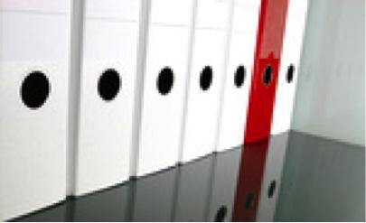 Auf dem Bild sind 7 Ordner erkennbar. 6 Ordner sind weiß, 1 ist rot. Dieser Ordner soll den Interim Manager in der Personalverwaltung repräsentieren.