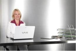 Auf dem Bild ist eine blonde lächelnde Frau zu erkennen, die an einem weißen Laptop sitzt. Sie soll die Social Media Recruiterin symbolisieren.