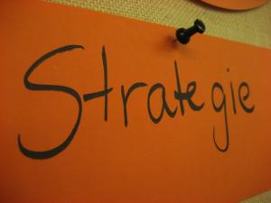 """Auf dem Foto ist ein orange-farbener Zettel mit der Aufschrift """"Strategie"""" an eine Pinwand geheftet zu erkennen."""
